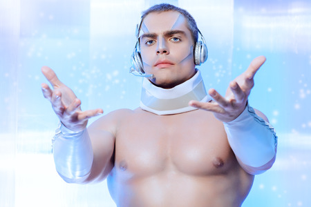 Technologies of the future, man of the future. Handsome muscular man with futuristic make-up in the headphones standing on a luminous transparent background. photo