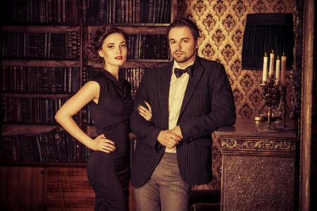 two men: Beautiful man and woman in elegant evening clothes in classic vintage apartments. Glamour, fashion. Love concept.