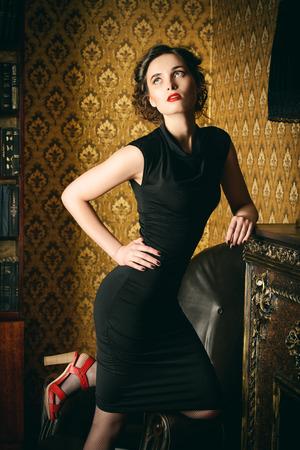 sexy fashion: Elegant young woman in black evening dress posing in vintage interior. Fashion shot.
