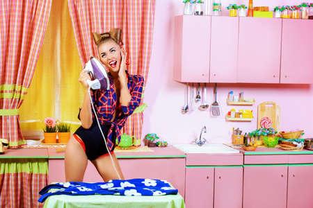 ama de casa: Encantadora chica pin-up tabla de su vestido y cantando en una cocina de color rosa glamour. Estilo retro. Moda.
