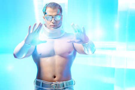 Technologies of the future, man of the future. Handsome muscular man with futuristic make-up wearing glasses stands on a luminous transparent background and touches something virtual. photo