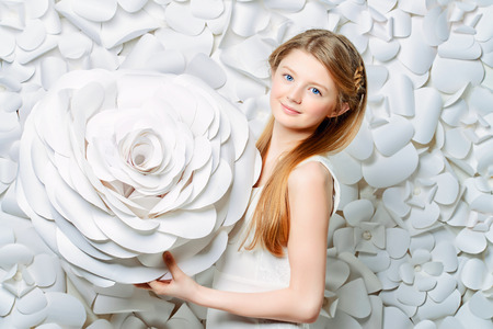 beautiful background: Beautiful blonde teen girl wearing white dress posing by a background of white paper flowers. Beauty, fashion.