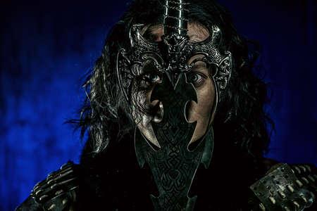 guerrero: Close-up retrato de la antigua guerrera masculina en la armadura que sostiene la espada. Personaje histórico. Fantasía.