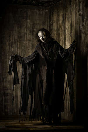 demon: Scary man in iron mask and black robe. Fantasy. Halloween.