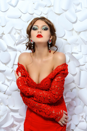 sensual: Seductive sensual woman in elegant red suit on a background of white flowers. Beauty, fashion.