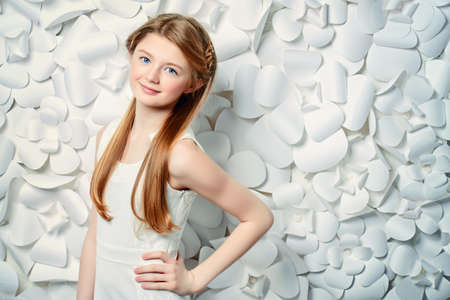 Beautiful blonde teen girl wearing white dress posing by a background of white paper flowers. Beauty, fashion.