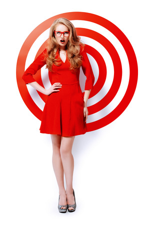 gorgeous: Gorgeous fashion model in red dress and elegant red glasses posing over red circles of the target. Beauty, fashion. Optics, eyewear.