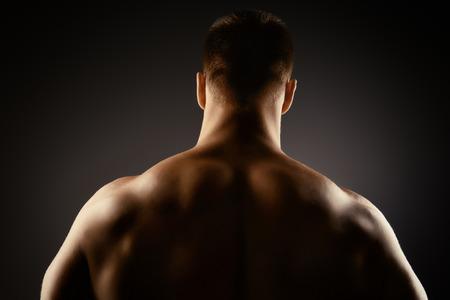 hombros: Atleta culturista hombre que demuestra su musculoso cuerpo perfecto - músculos de la espalda y los brazos. Sobre fondo negro.