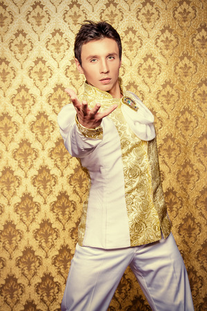 stage costume: Portrait of a handsome man ballet dancer in a stage costume. Show-ballet. Golden vintage background.