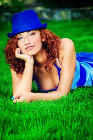foxy girls: Beautiful smiling girl lying on a green lawn. Summer day.