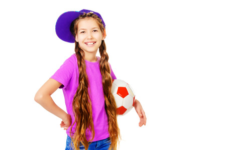 active lifestyle: Happy smiling girl teenager wearing casual clothes posing with a football. Active lifestyle. Studio shot. Isolated over white. Stock Photo