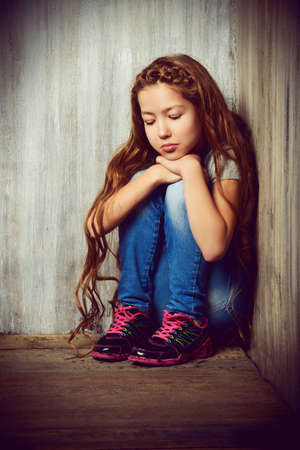 awkward: Portrait of a sad girl child sitting in the corner of the room. Loneliness, depression. Awkward age.