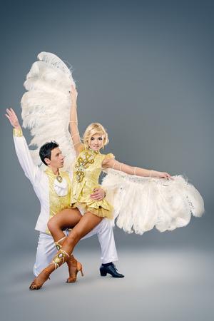 gogo girl: Schöne Paare der Tänzer tanzen im Studio in weiß üppigen Kostümen mit Flügeln. Show-Ballett. Lizenzfreie Bilder