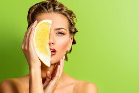fruta: Mujer joven de moda la celebraci�n de la papaya sobre fondo verde. Frutas tropicales. Alimentaci�n saludable. Belleza, cosm�ticos.