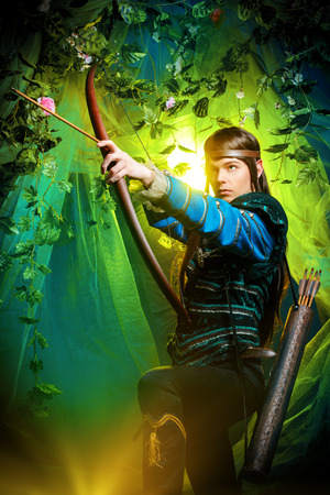 cosplay: Portrait of a male elf with a bow and arrows in a magical forest.