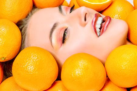 comiendo frutas: Close-up retrato de una bella mujer sonriente entre naranjas frescas. Una alimentación saludable, el jugo. Maquillaje, cosméticos. Dientes sanos.