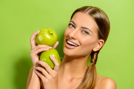 Happy beautiful young woman holding fresh apples over green background. Healthy lifestyle. Healthy eating. Fruits and vegetables. Stock Photo