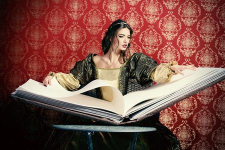 femme brune sexy: Fée belle sorcière lit livre magique de sorts. Style vintage. Renaissance. Barocco. Halloween.