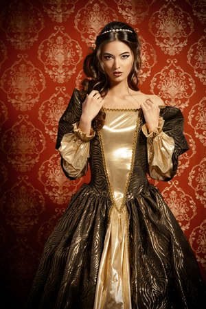 Beautiful young lady in the lush expensive dress posing over vintage background. Renaissance. Barocco. Fashion. Stock Photo