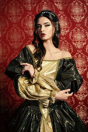 vestido medieval: Señora joven hermosa en el vestido caro exuberante que presenta sobre el fondo de la vendimia. Renacimiento. Barocco. Moda.