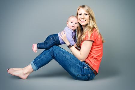 mignonne petite fille: Heureux belle mère tient son bébé adorable. Concept de famille. Studio shot.