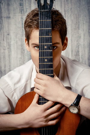 bard: Romantic young man playing an acoustic guitar.