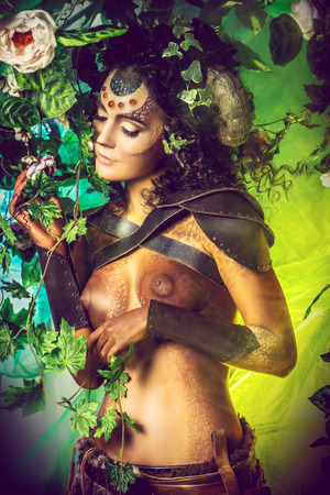 Fabulous female Faun in a fairy garden. Fantasy world. Body painting project.