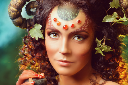 faun: Art portrait of a fabulous female Faun in a fairy forest. Fantasy. Body painting.