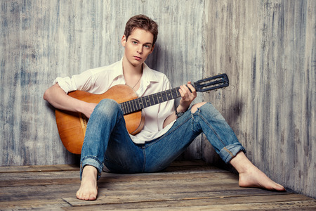 romantic man: Romantic young man playing an acoustic guitar, sitting on the wooden floor