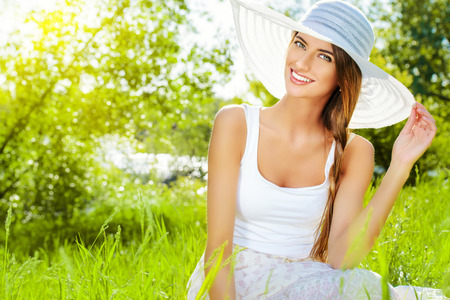 summer beauty: Portrait of a beautiful elegant young woman in light white dress and hat in the summer park. Beauty, fashion. Holidays.