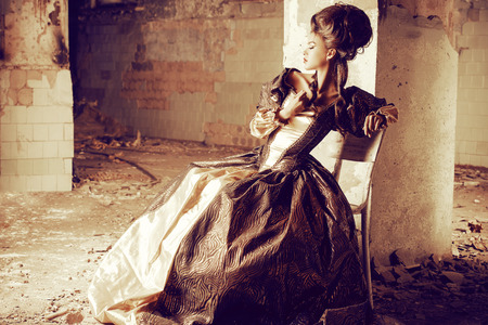 vintage dress: Art Fashion. Beautiful young woman in elegant historical dress and with barocco updo hairstyle posing in the ruins of the castle. Renaissance. Barocco.