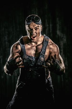 hombre sucio: Brutal hombre sucio muscular de expresar la agresi�n sobre el fondo negro.