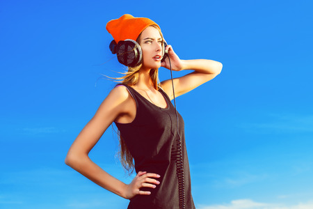 rap: Modern young woman listening to music on headphones outdoor.
