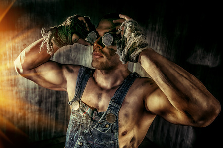 COAL MINER: Portrait of a strong muscular man coal miner standing over dark grunge background.  Stock Photo