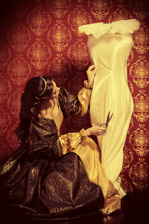 haute couture: Beautiful young woman in a lush renaissance dress sewing new dress. Vintage background. Fashion history. Haute Couture.