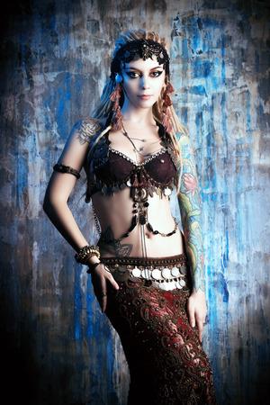 BELLY DANCING: Art portrait of a beautiful traditional female dancer. Ethnic dance. Belly dancing. Tribal dancing.