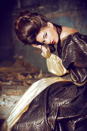 vestido medieval: Arte de la moda de la mujer joven en traje histórico y elegante con el peinado updo Barocco que presenta en las ruinas del castillo.
