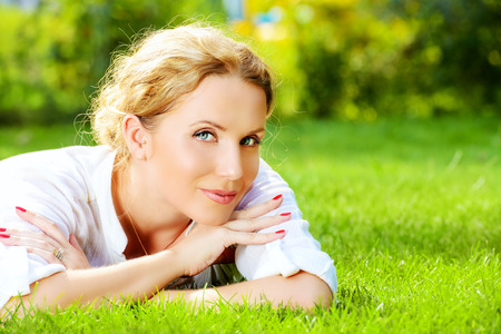 absolutely: Close-up portrait of a beautiful smiling woman lying on a grass outdoor. She is absolutely happy. Stock Photo