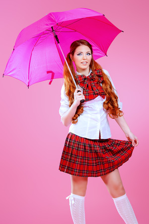 schoolgirl uniform: Cute smiling teen girl in school plaid skirt and white blouse posing over pink background. Anime style.