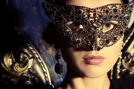 black mask: Close-up portrait of a beautiful woman in venetian mask. Carnival, masquerade. Jewellery, gems. Stock Photo