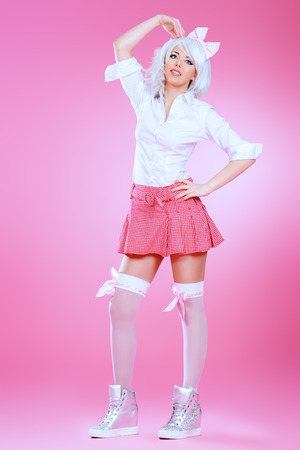the girl in stockings: Full length portrait of a cute teen girl wearing white wig and school uniform with stockings posing over pink background. Anime style. Stock Photo