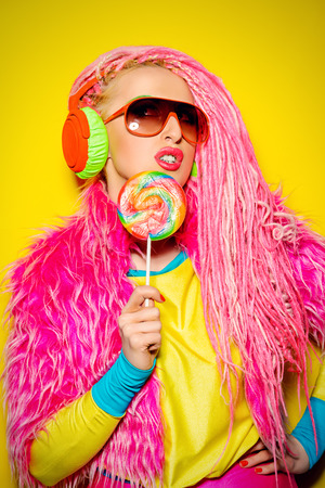 sexy lollipop: Attractive glamorous girl wearing ultra bright clothes and with pink dreadlocks eating lollipop. Bright style. Party style.