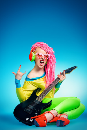 show business: Female rock star playing the electric guitar. Bright style. Show business.