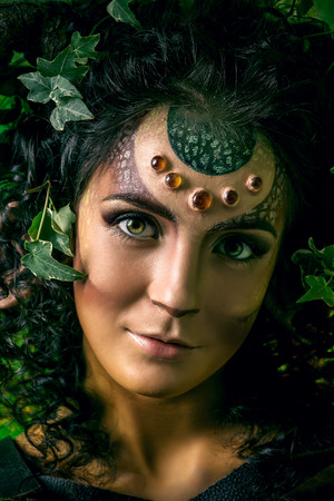 myth: Close-up portrait of a fairy female Faun. Myth and fantasy. Body painting project. Studio shot.