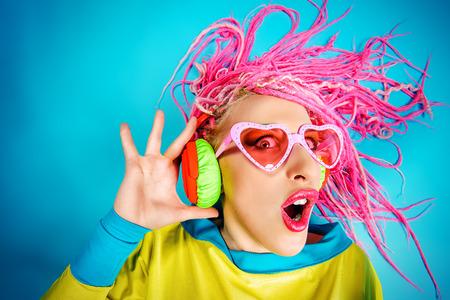 crazy people: Loco expresiva chica DJ de moda en ropa brillante, auriculares y rastas brillantes. Disco, fiesta. Bright fashion. Foto de archivo