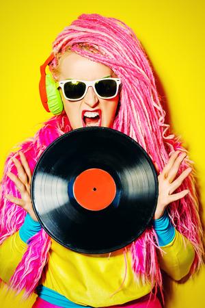 ultra: Glamorous modern DJ girl posing with vinyl record. Disco, party. Bright fashion.