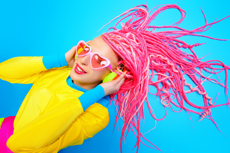 expressive: Ultra trendy DJ party girl in bright clothes, headphones and with bright dreadlocks. Disco, party. Show business. Bright fashion.