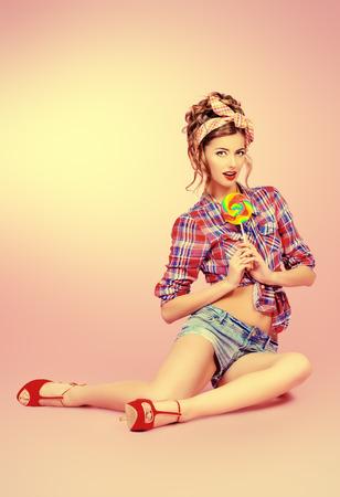 sexy young girl: Сексуальная очаровательная девушка в шортах и высокие каблуки, сидя на полу с ярким леденец на розовом фоне. Красота, мода. Полная длина портрет. Фото со стока
