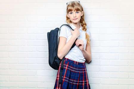 falda: Muchacha bastante adolescente con uniforme escolar y la bolsa de la escuela. Educación. Estudio de disparo. Foto de archivo
