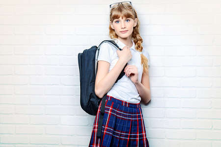 checkered skirt: Pretty teen girl wearing school uniform and school bag. Education. Studio shot.